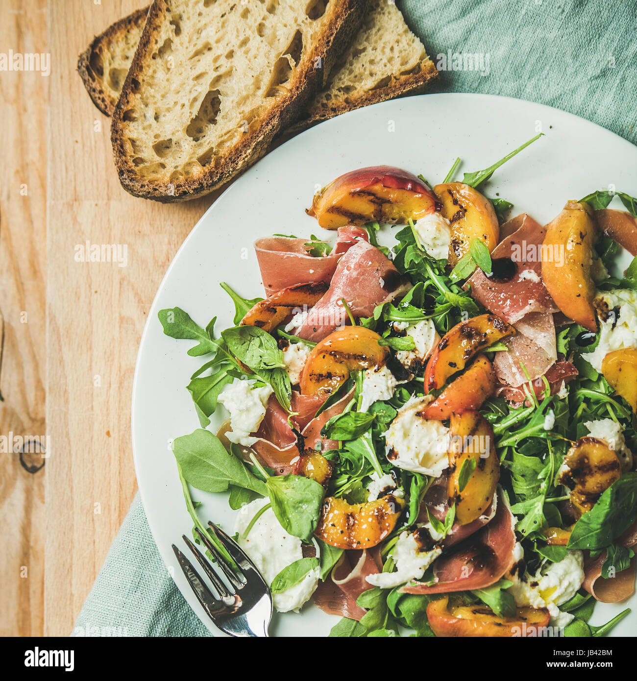 Arugula, prosciutto, mozzarella and grilled peach salad, top view - Stock Image