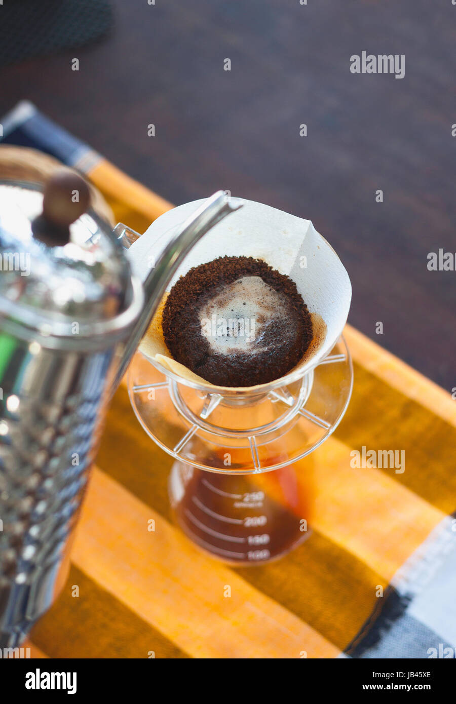 Pour Over Coffee Drip Brewing with paper filter while coffee blooming - Stock Image