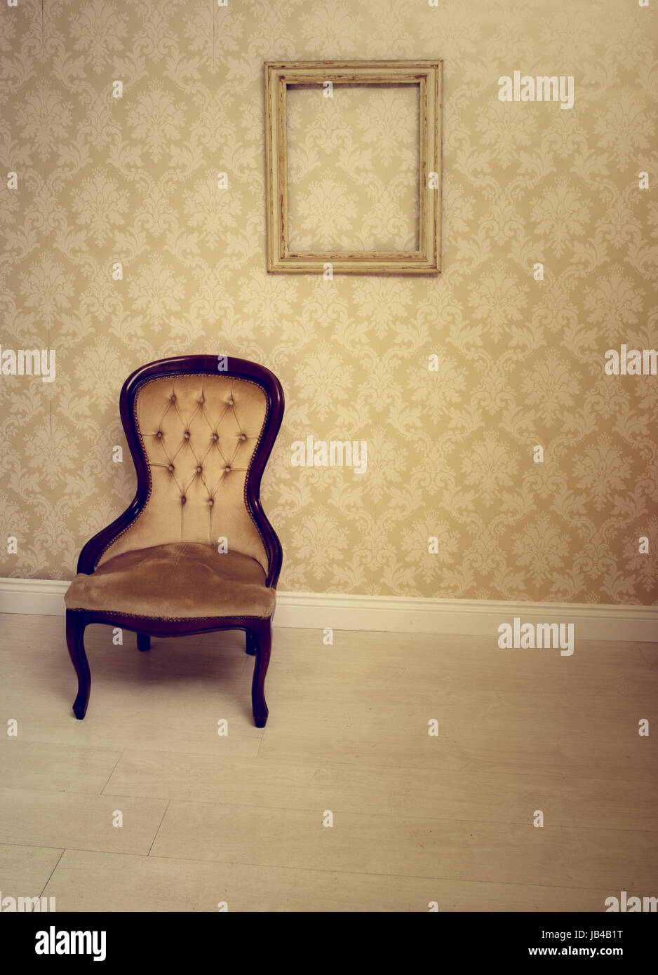 Antique upholstered chair in a wallpapered room with an empty vintage  wooden picture frame hanging on the wall suitable as an interior decorating  background - Antique Upholstered Chair In A Wallpapered Room With An Empty