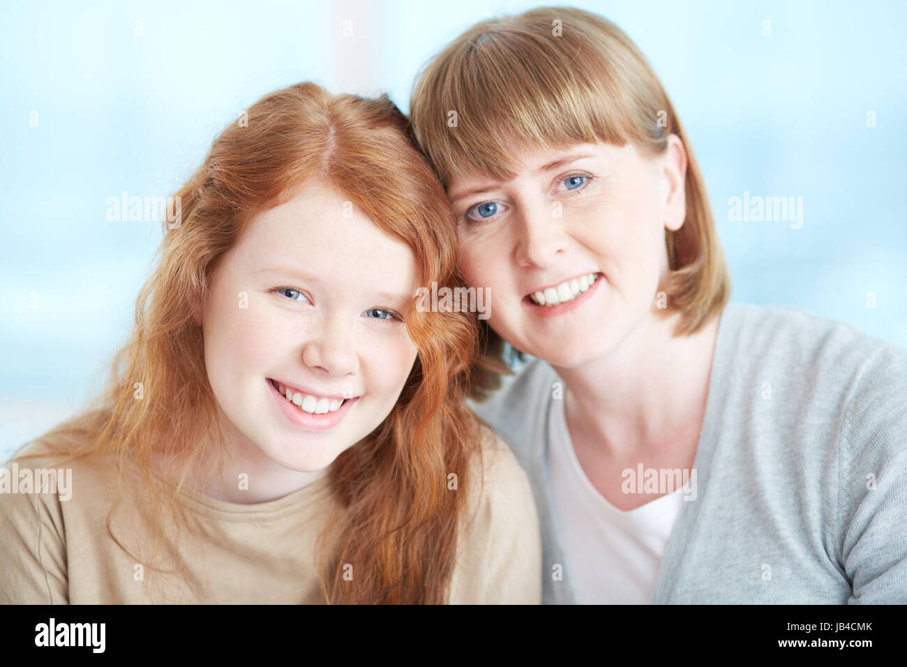 Lovely girl and her mother looking at camera with toothy smiles - Stock Image
