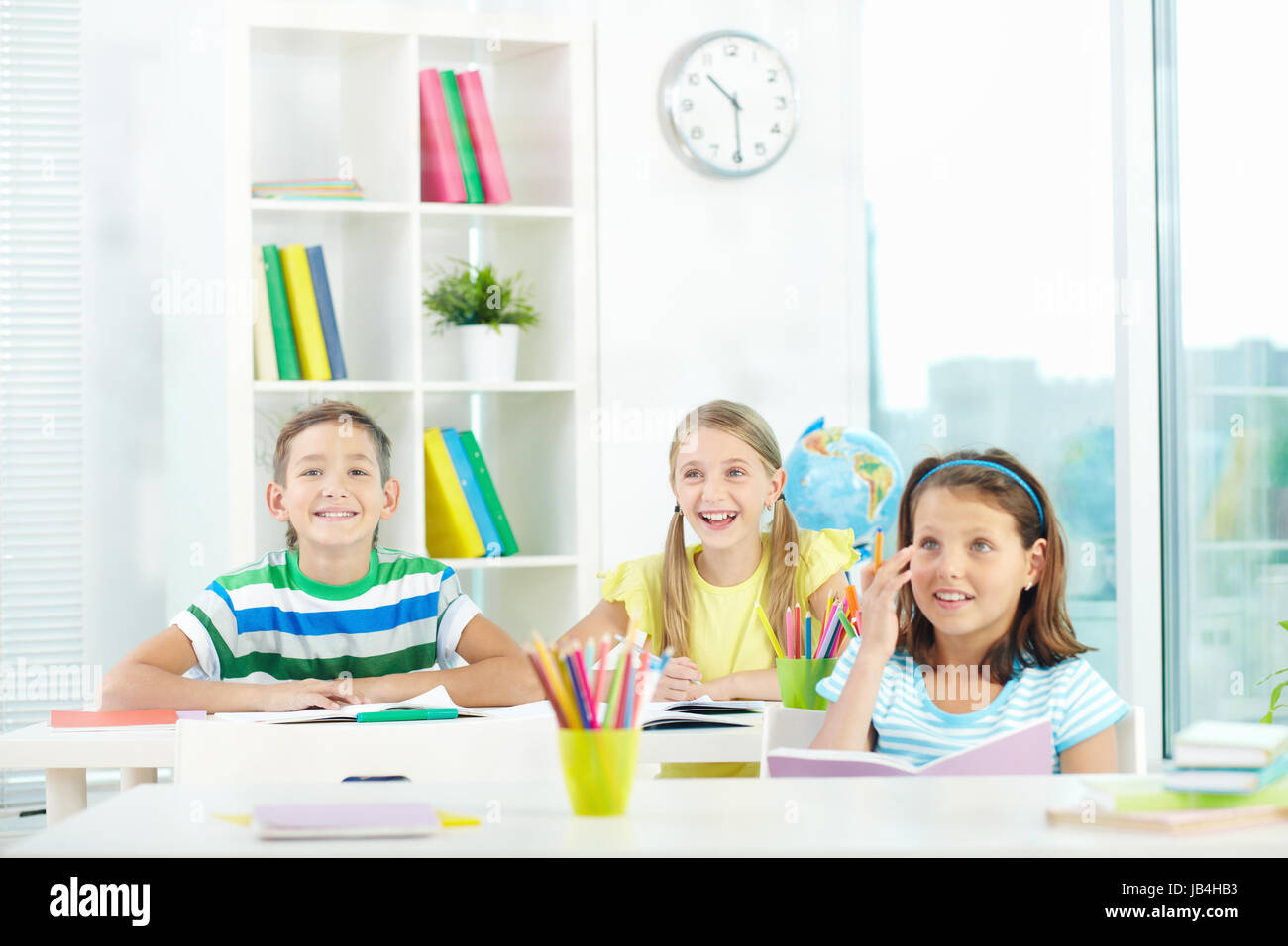 Portrait of joyful schoolmates looking at something attentively at lesson - Stock Image