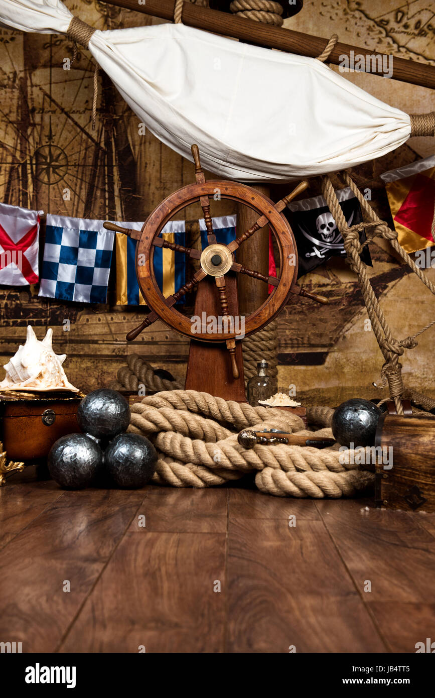 Pirates ship deck with steering wheel and flag - Stock Image