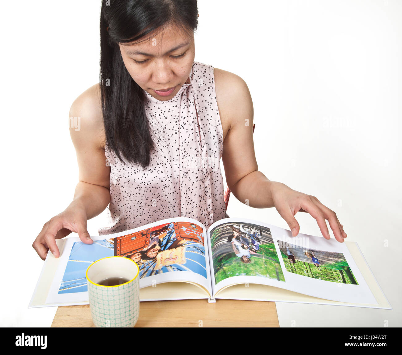 Portrait of a cute young  asian girl in studio reading a book - Stock Image