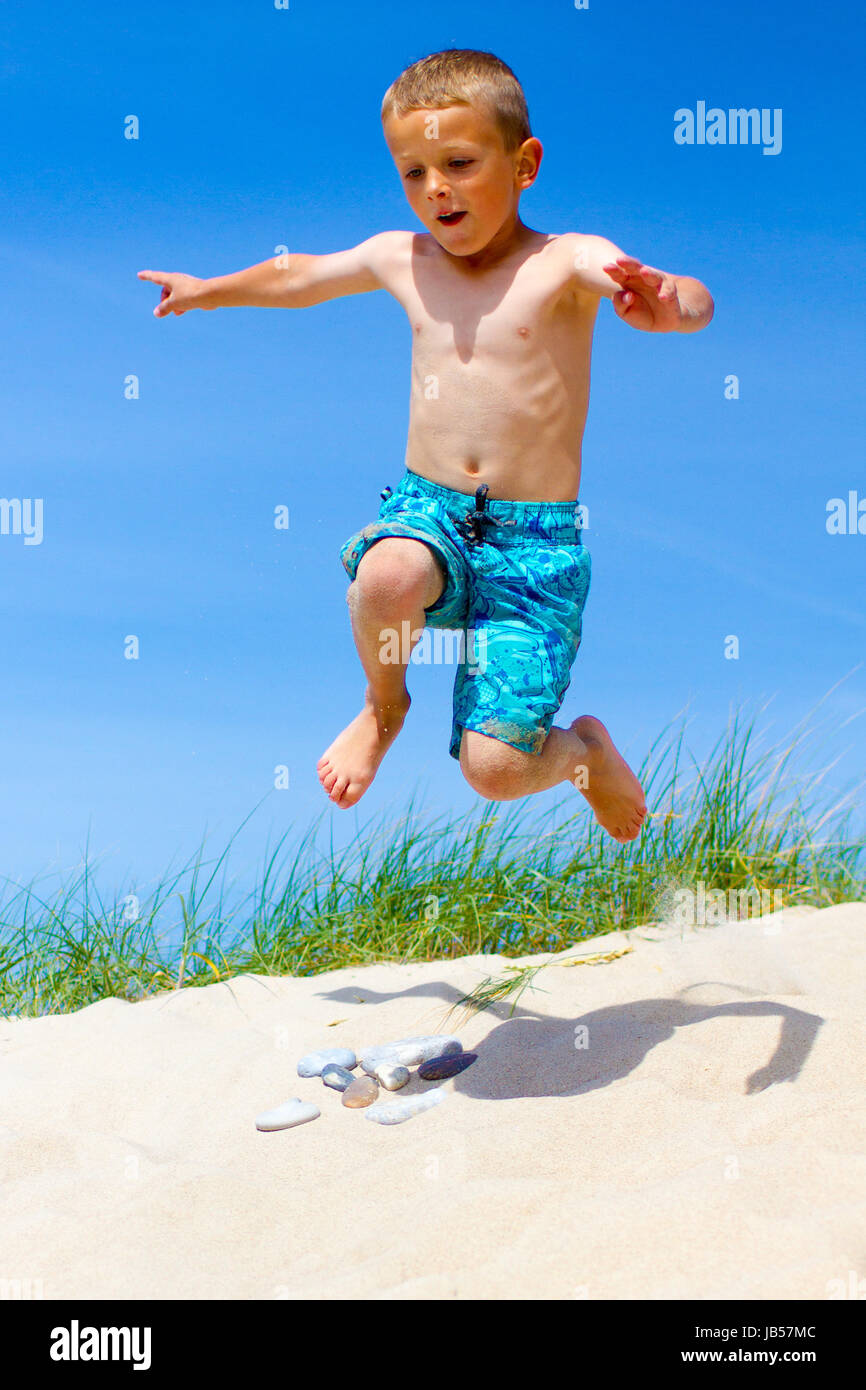 Young Caucasian boy is having fun doing wild jumps in sand dunes. Boy is wearing bright blue swim shorts. - Stock Image