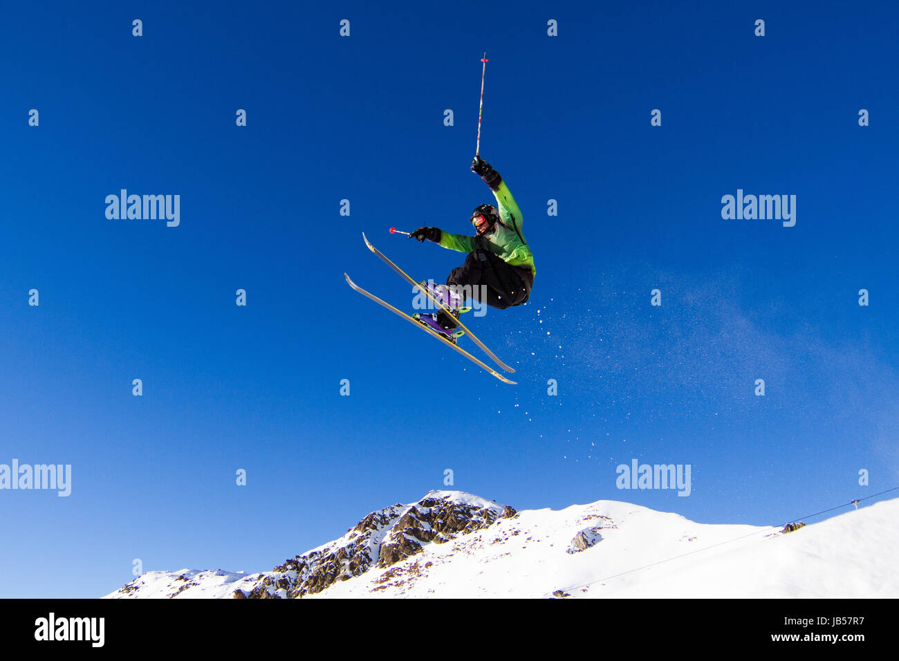 Skier pulling off a tricky jump in snowpark. Trademarks have been removed. - Stock Image