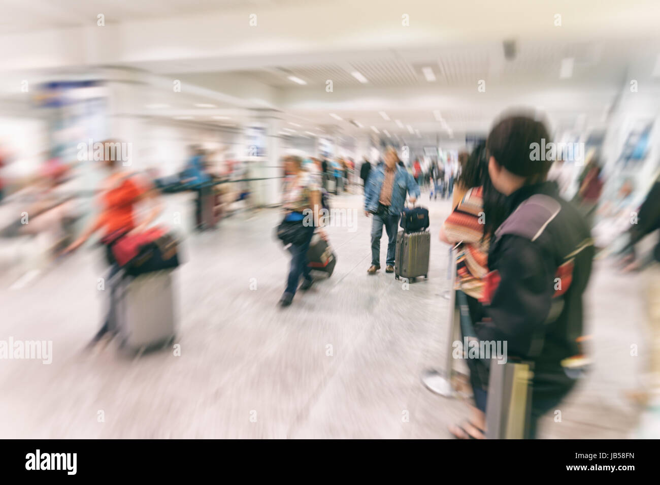 Blurred image of passengers arriving at arrivals gate at international airport - Stock Image