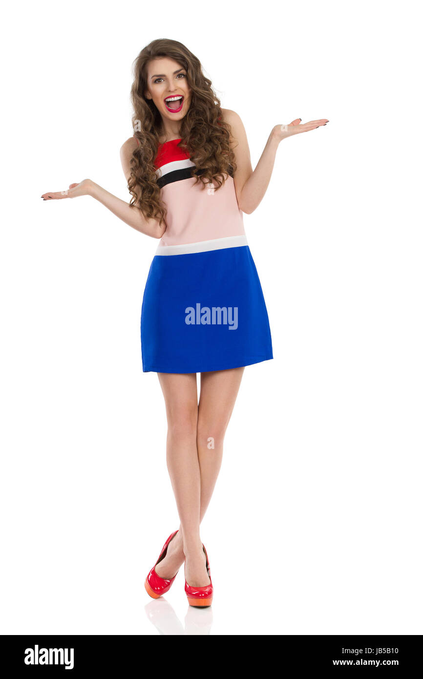 Excited beautiful young woman in colorful mini dress and high heels is standing with hands raised. Front view. Full - Stock Image
