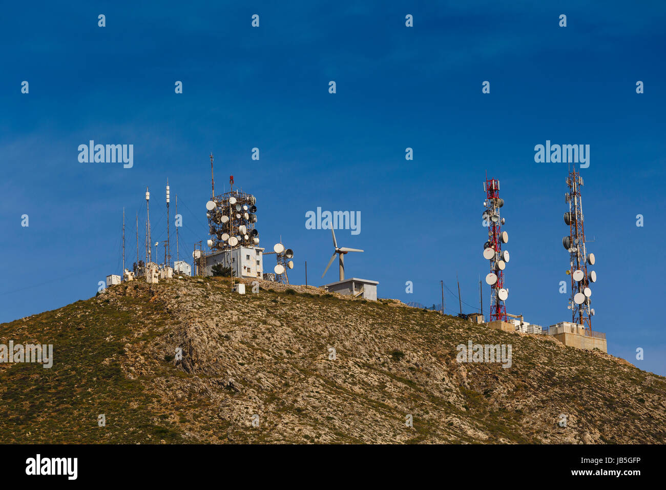 Telecommunication antenas on a hilltop over Ermoupoli town on Syros island in Greece. - Stock Image