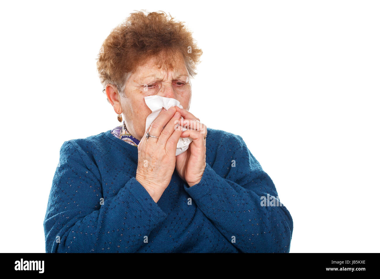 Picture of an elderly woman blowing her nose - Stock Image