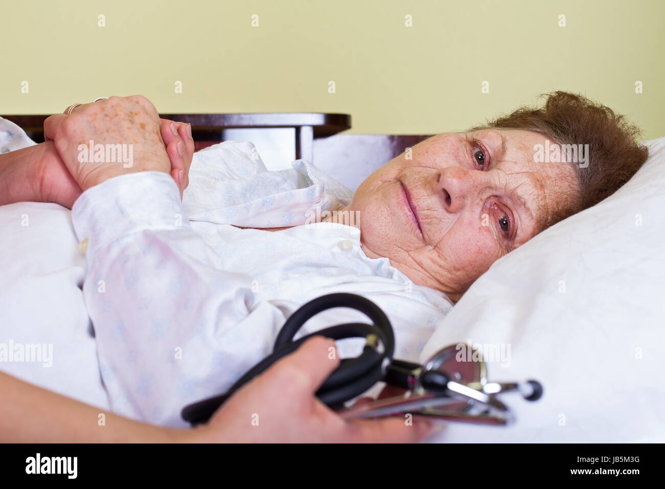 Picture of a bed ridden elderly woman with her care holding a stethoscope - Stock Image
