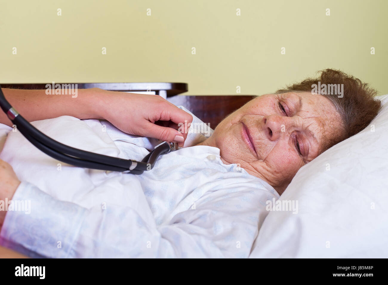 Picture of an elderly woman having fever, lying in bed - Stock Image