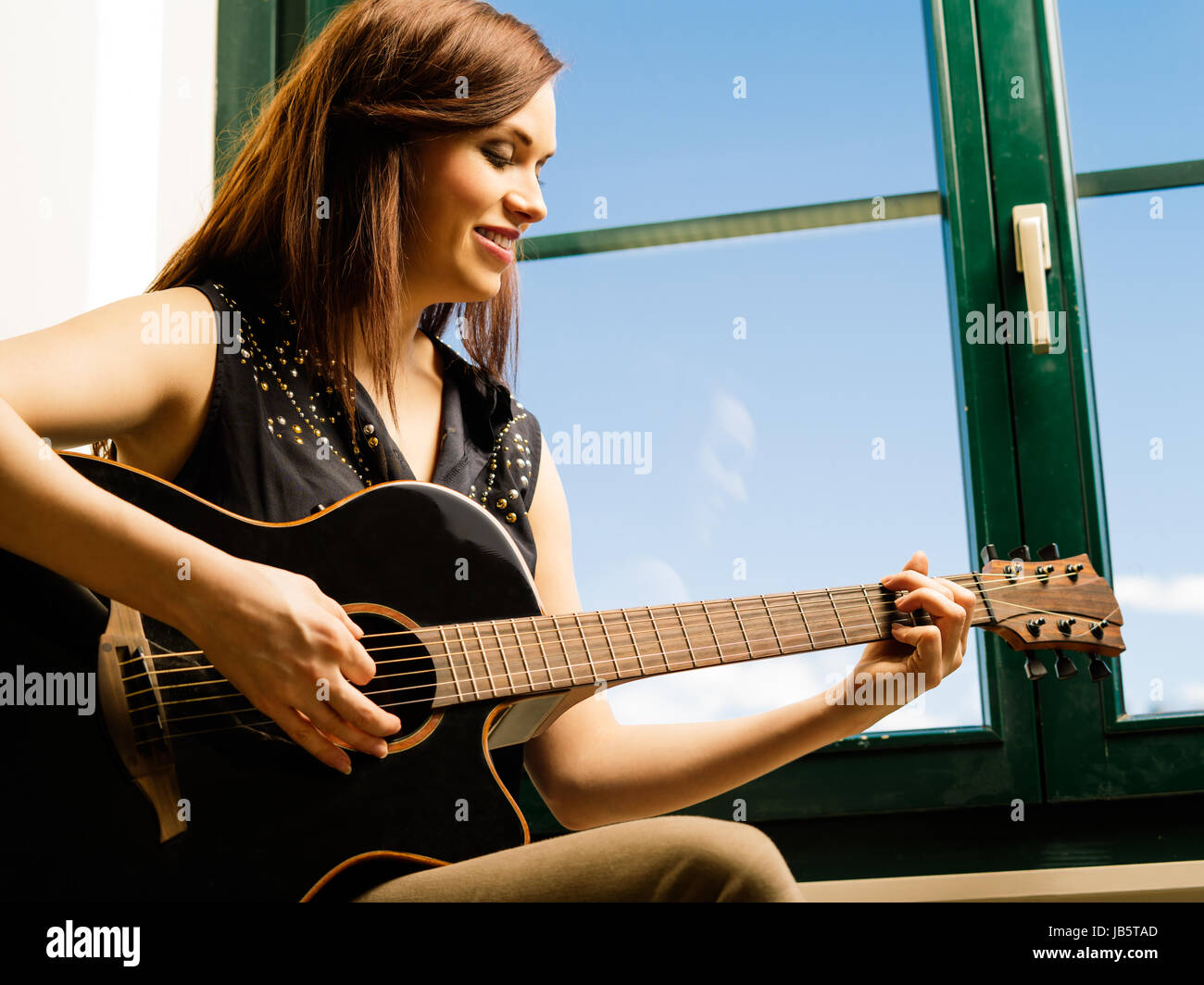 Photo of a smiling woman in her late twenties playing an acoustic guitar by a large window. - Stock Image
