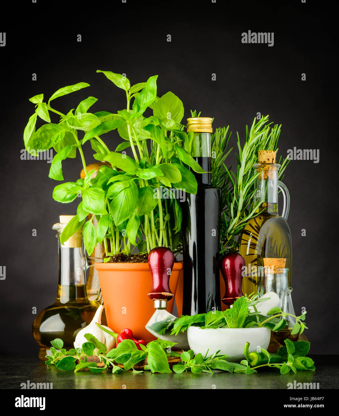 Still Life with Fresh Green Basil Herbs, Olive oil, Mezzaluna Herb-chopper and Pestle and Mortar Kitchen Utensil - Stock Image