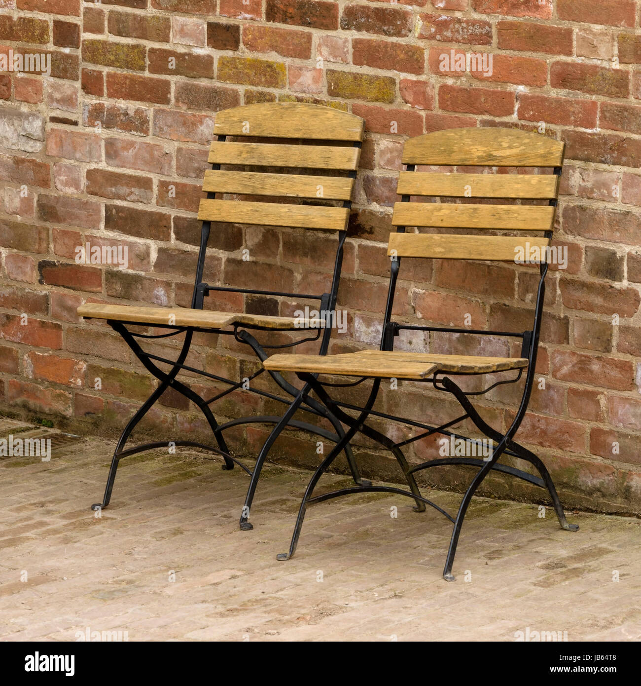Two Folding Metal Chairs With Wooden Slats In Front Of Red Brick Wall