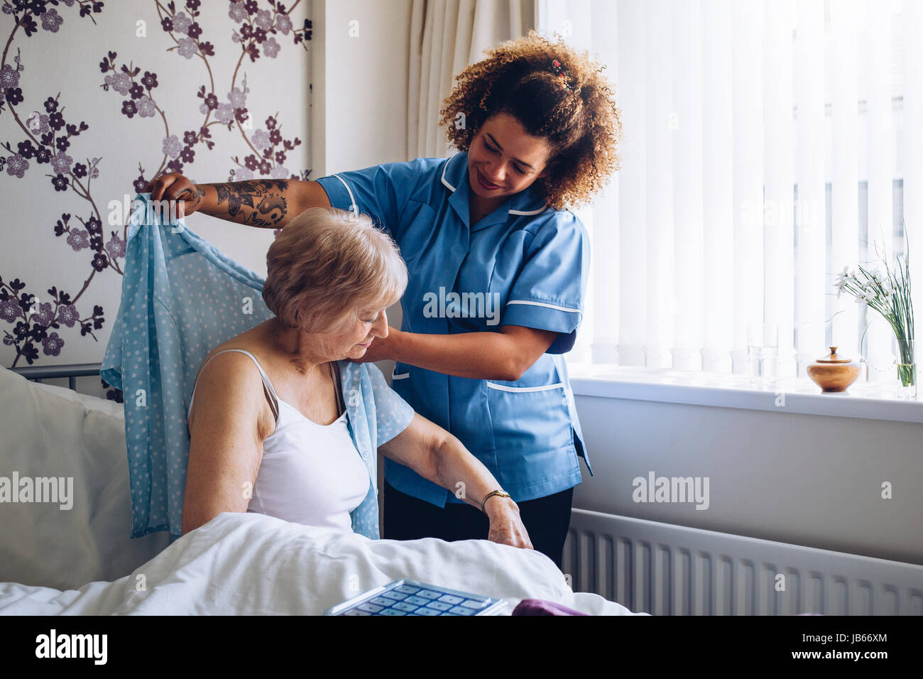 Home Caregiver helping a senior woman get dressed in her bedroom. - Stock Image