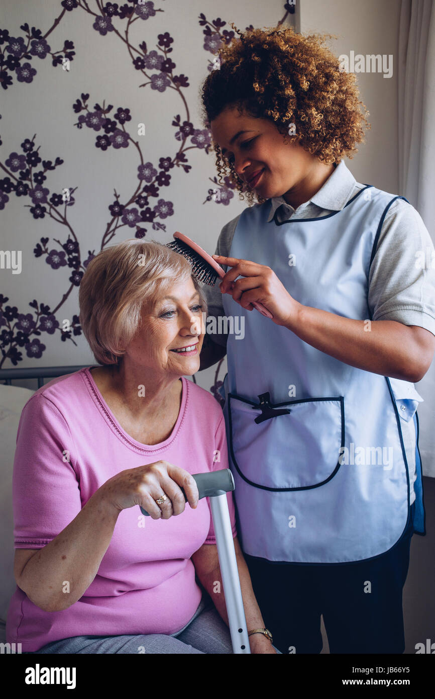 Home Caregiver brushing the hair of a senior woman in her bedroom. - Stock Image
