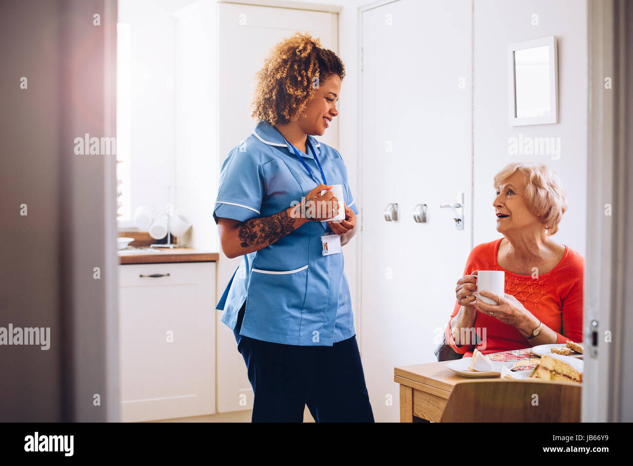home caregiver talking to her patient in her kitchen as they drink tea and eat sponge cake. - Stock Image