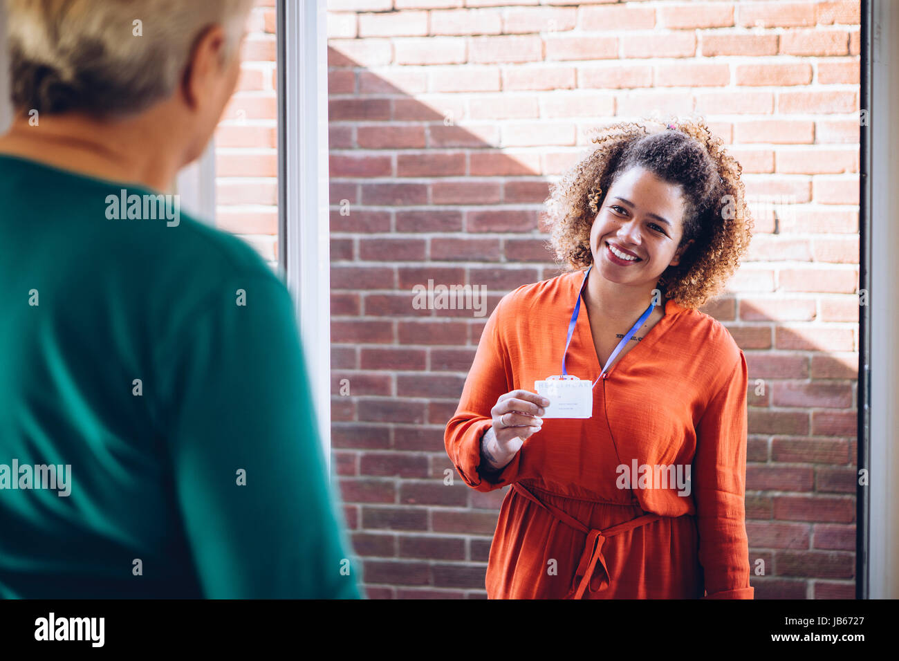 Healthcare worker showing her badge at the front door of a senior womans home. - Stock Image