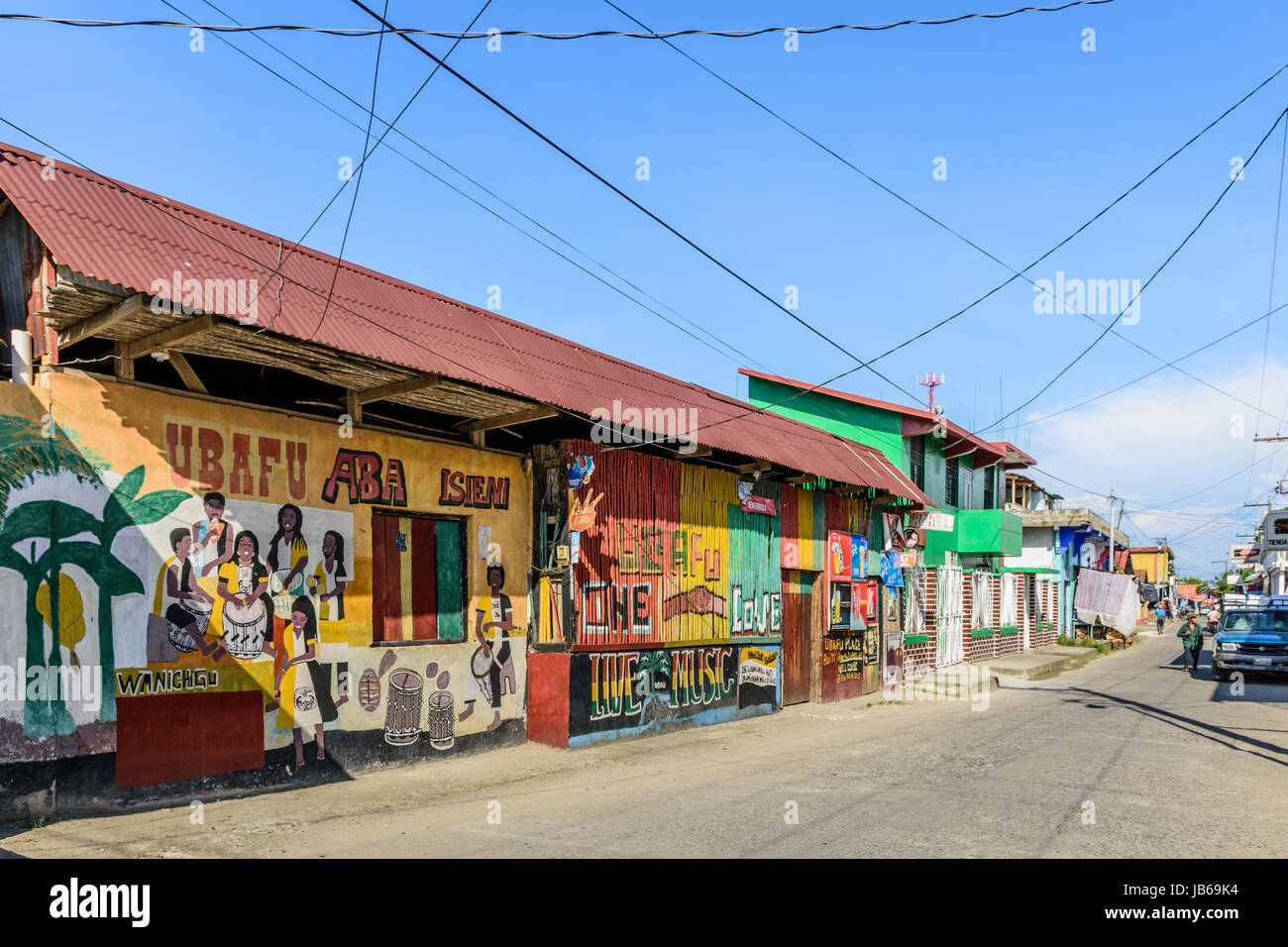 Livingston, Guatemala - August 31, 2016: Building walls painted with local Garifuna musicians in street in Caribbean - Stock Image