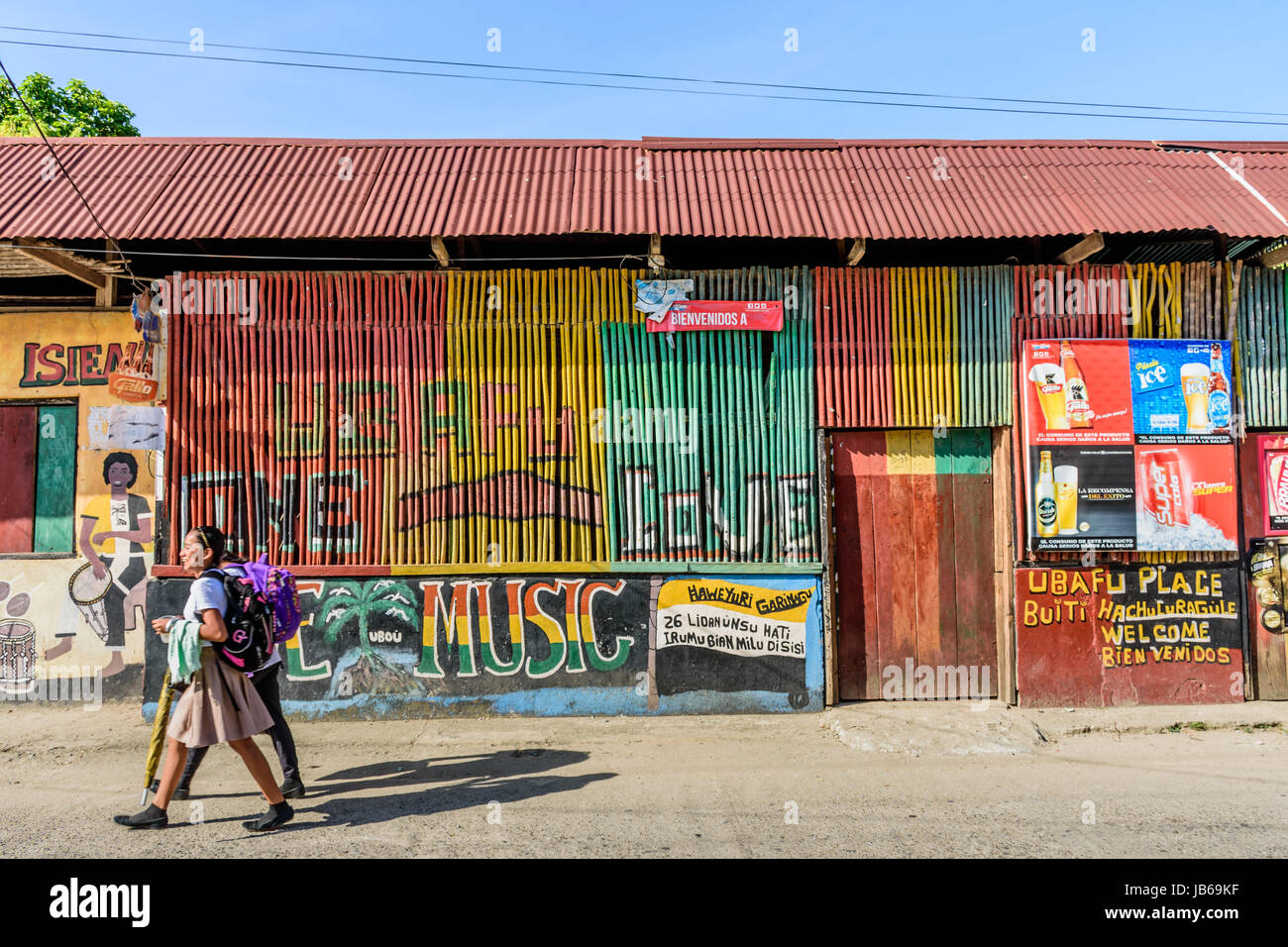 Livingston, Guatemala - August 31, 2016: Girls walk past colorfully painted walls in street in Caribbean town of - Stock Image