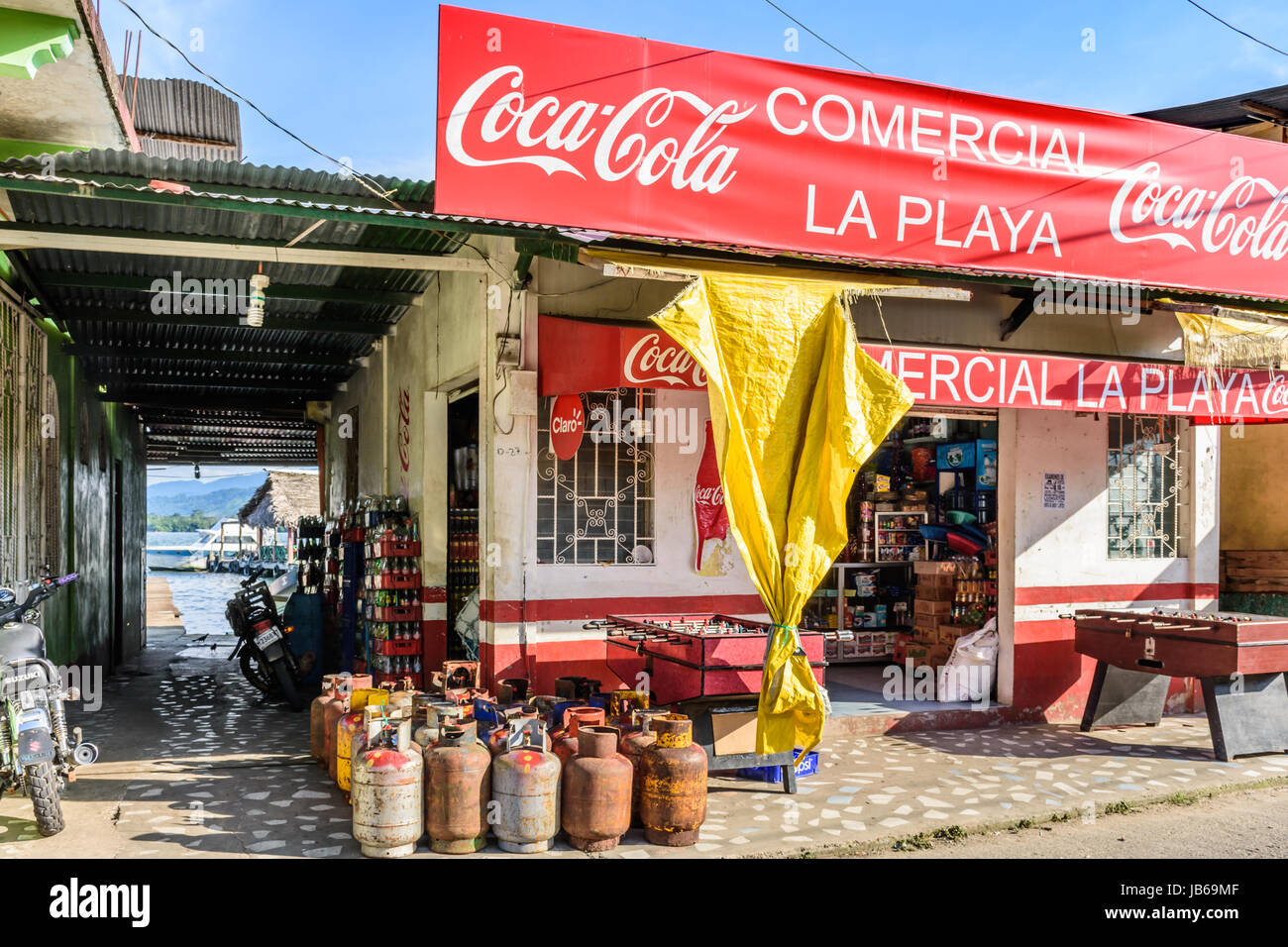Livingston, Guatemala - August 31, 2016: Alleyway leads to moored boats at wooden dock next to riverside store in - Stock Image