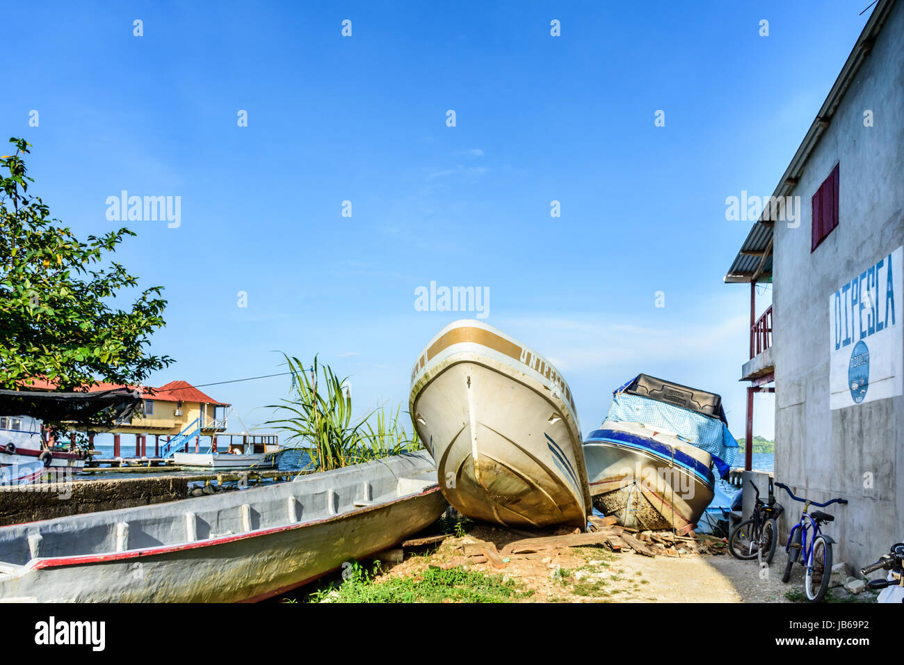 Livingston, Guatemala - August 31, 2016: Fishing boats pulled ashore on riverbank of Rio Dulce in Caribbean town - Stock Image