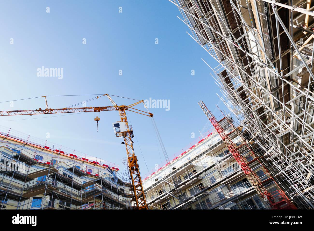 Construction site with cranes and scaffolding. - Stock Image