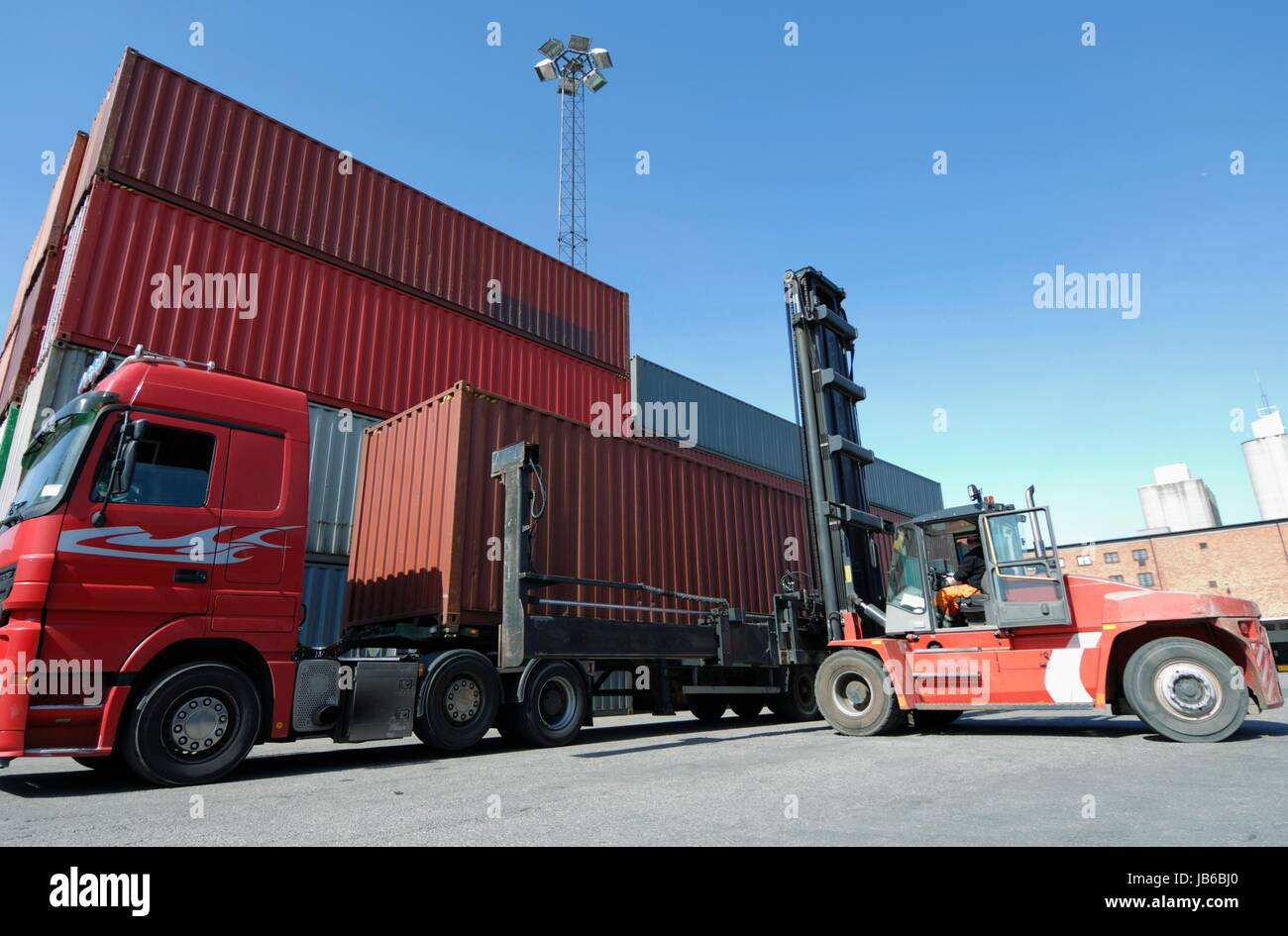 Forklift truck lifting shipping container. Stock Photo