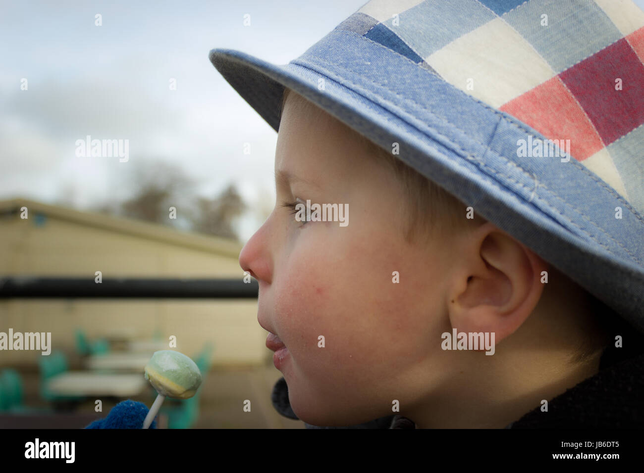 Small boy eating a lollipop - Stock Image