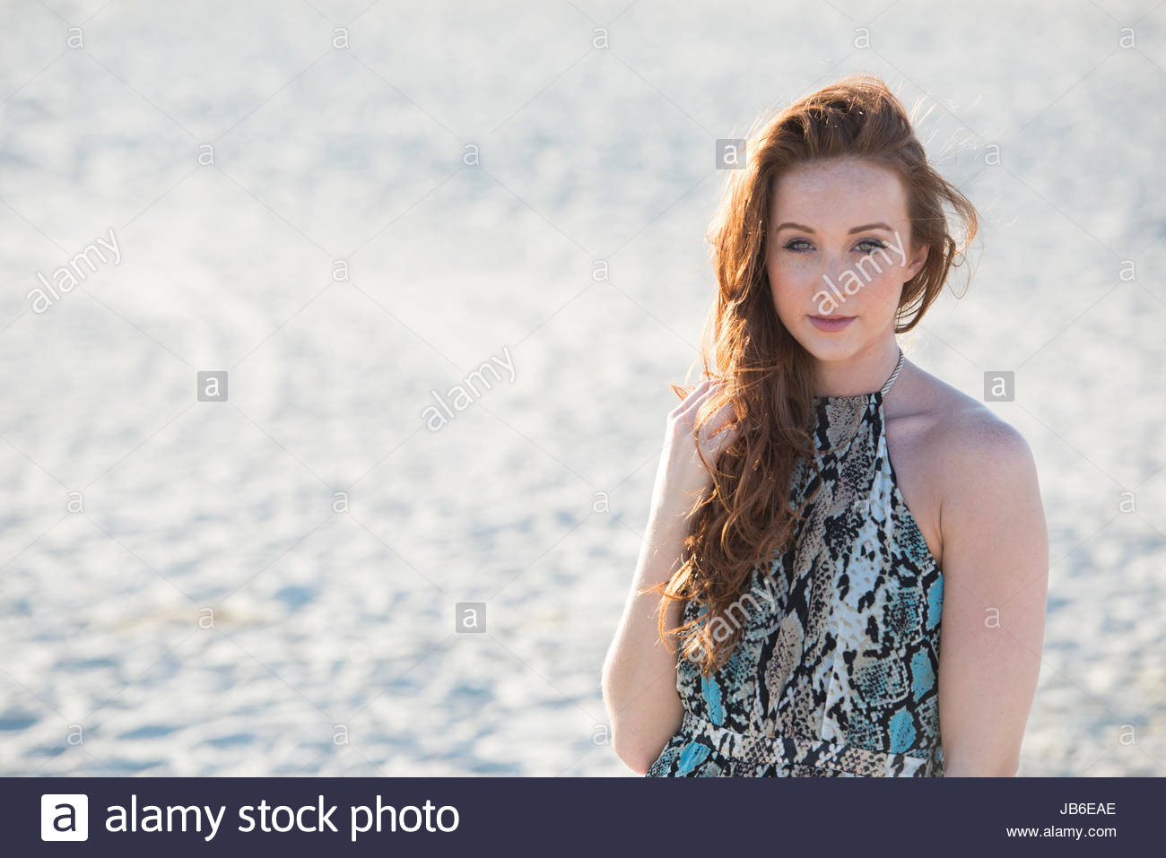 Beautiful young red-haired woman wearing turquoise and beige sundress poses on beach with sand and setting sun behind - Stock Image