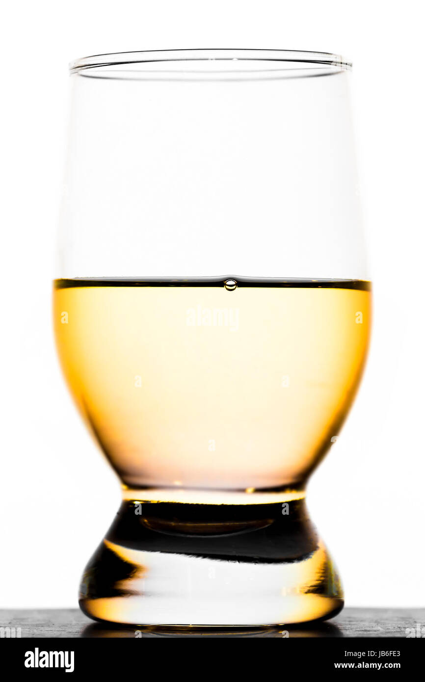 A glass of moonshine on a white background - Stock Image