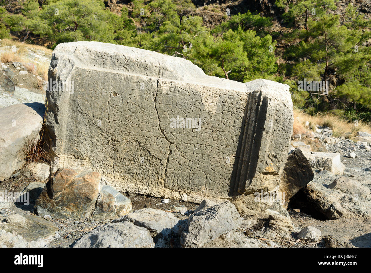 Stone with ancient Greek script. Ruins of temple of Hephaestus on Chimaera Mount. Turkey - Stock Image