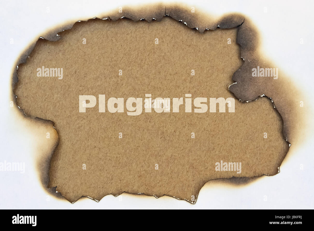 Word Plagiarism written in the middle of burnt paper - Stock Image