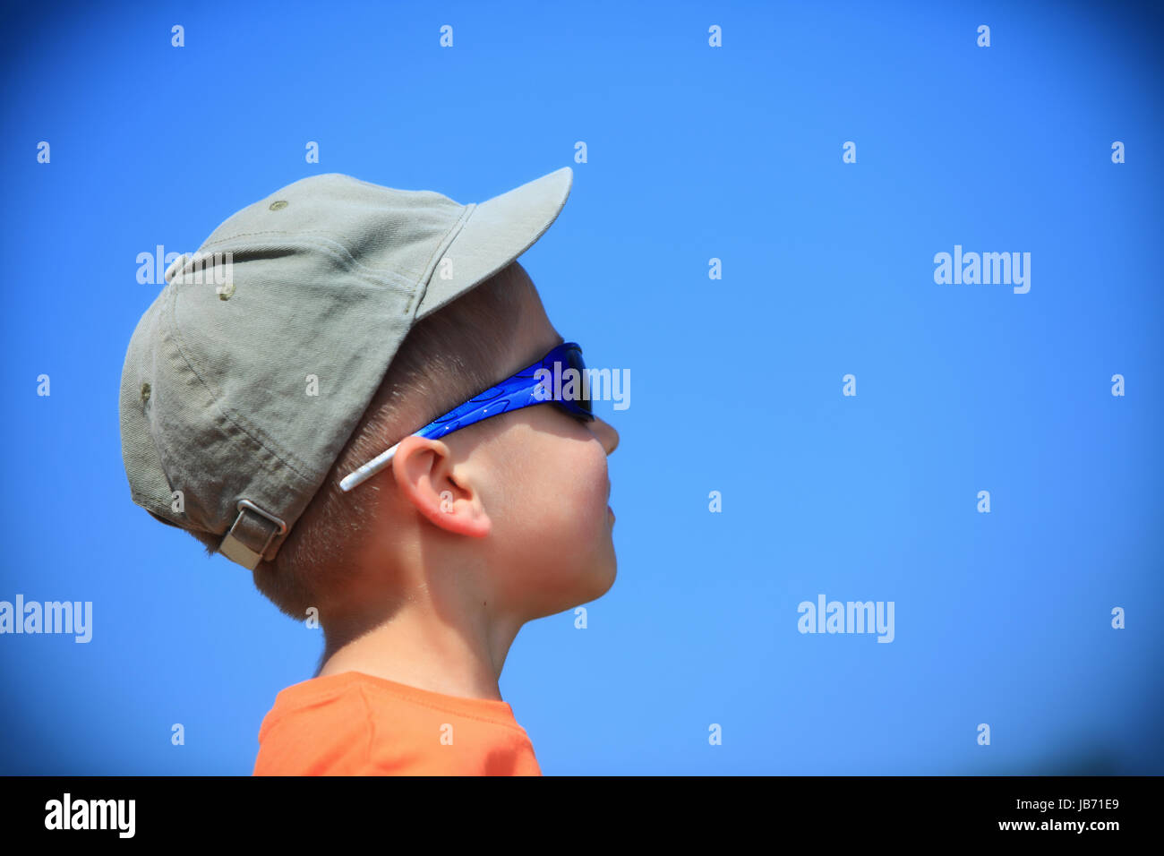 af5094888f41 Little boy kid with sunglasses and cap outdoor sky background Stock ...