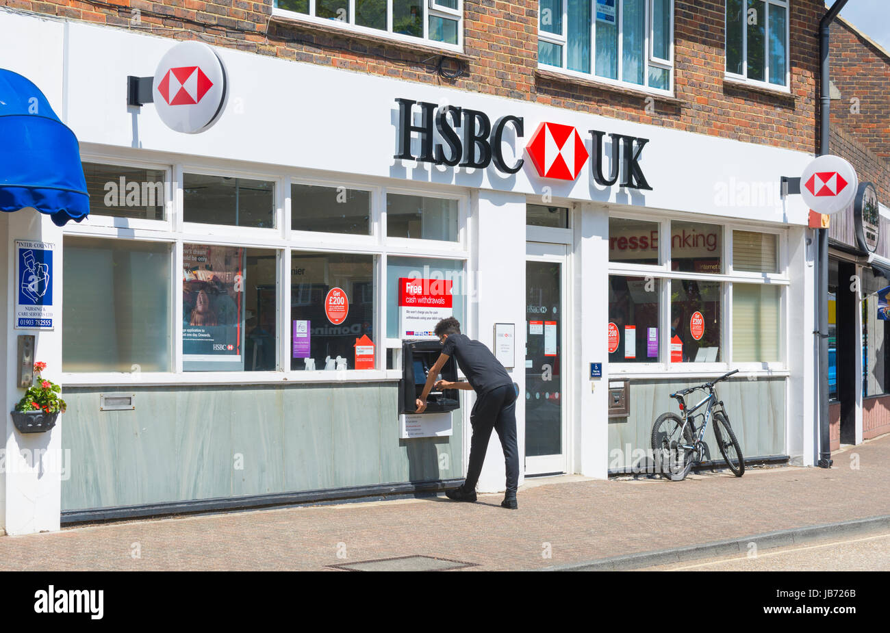 HSBC bank in the UK with person using cashpoint. Stock Photo