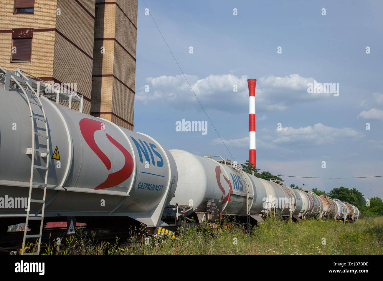 BELGRADE, SERBIA - JUNE 03, 2017: Tank wagons train from Nafta Industria Srbije passing near a factory chimney in Stock Photo