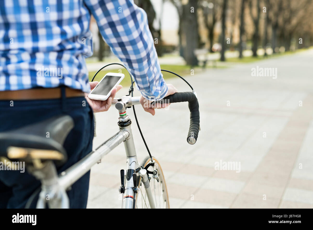 Senior man with smartphone and bicycle in town. - Stock Image