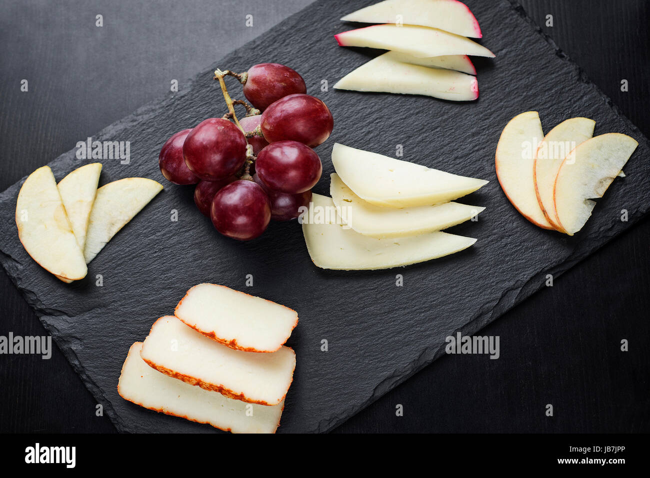 gourmet mixed cheese board tapas starter with apple and grapes snack - Stock Image