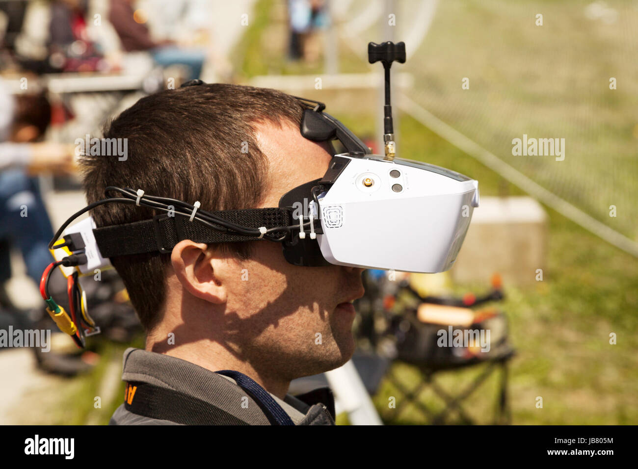 Drone pilot wearing first-person view headset. Young man driving a quadcopter using video-goggles - Stock Image