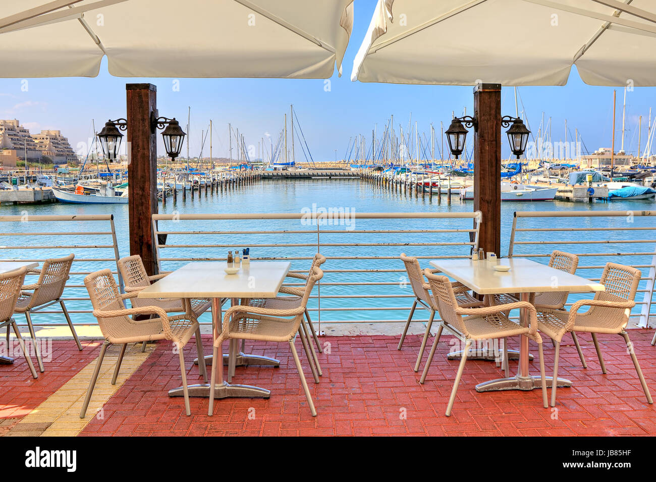 White tables and chairs of outdoor restaurant on promenade along marina on Mediterranean sea in Ashkelon, Israel. - Stock Image