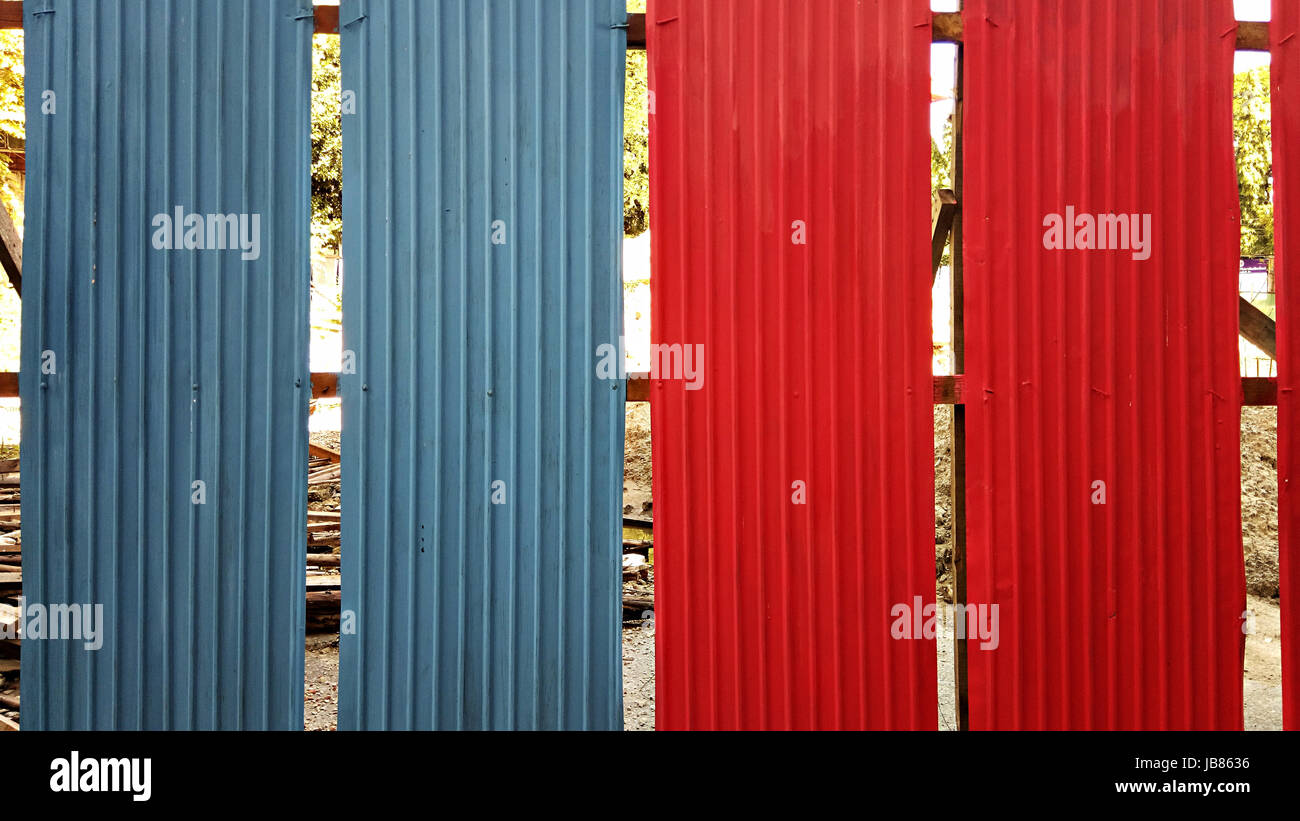 Blue and red galvanized iron plate fence - Stock Image