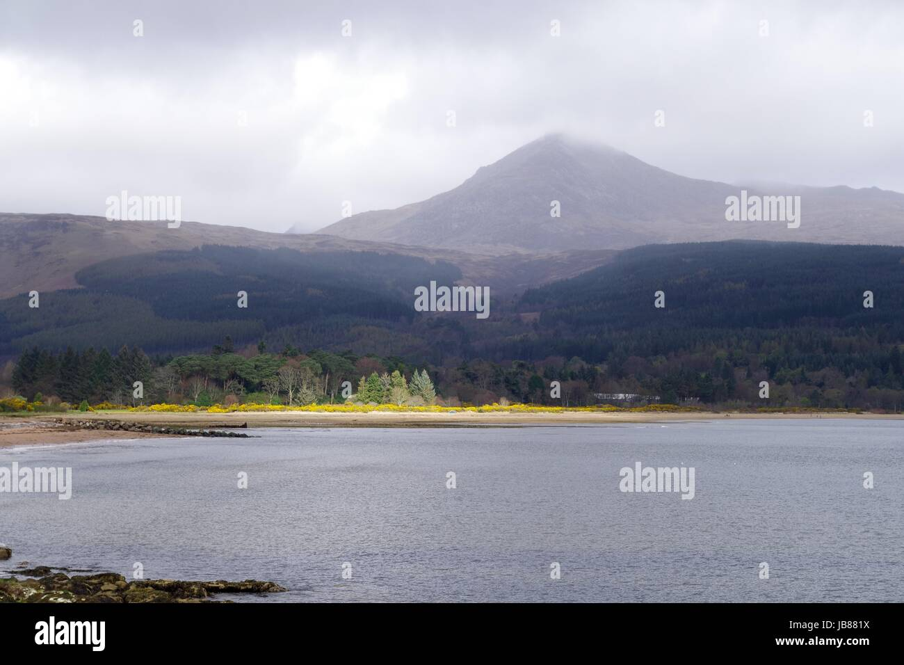 Cloud Capped Goat Fell Mountain Peak, Behind the Sunlit Foreshore of Brodrick Bay. Isle of Arran, Scotland. April, - Stock Image