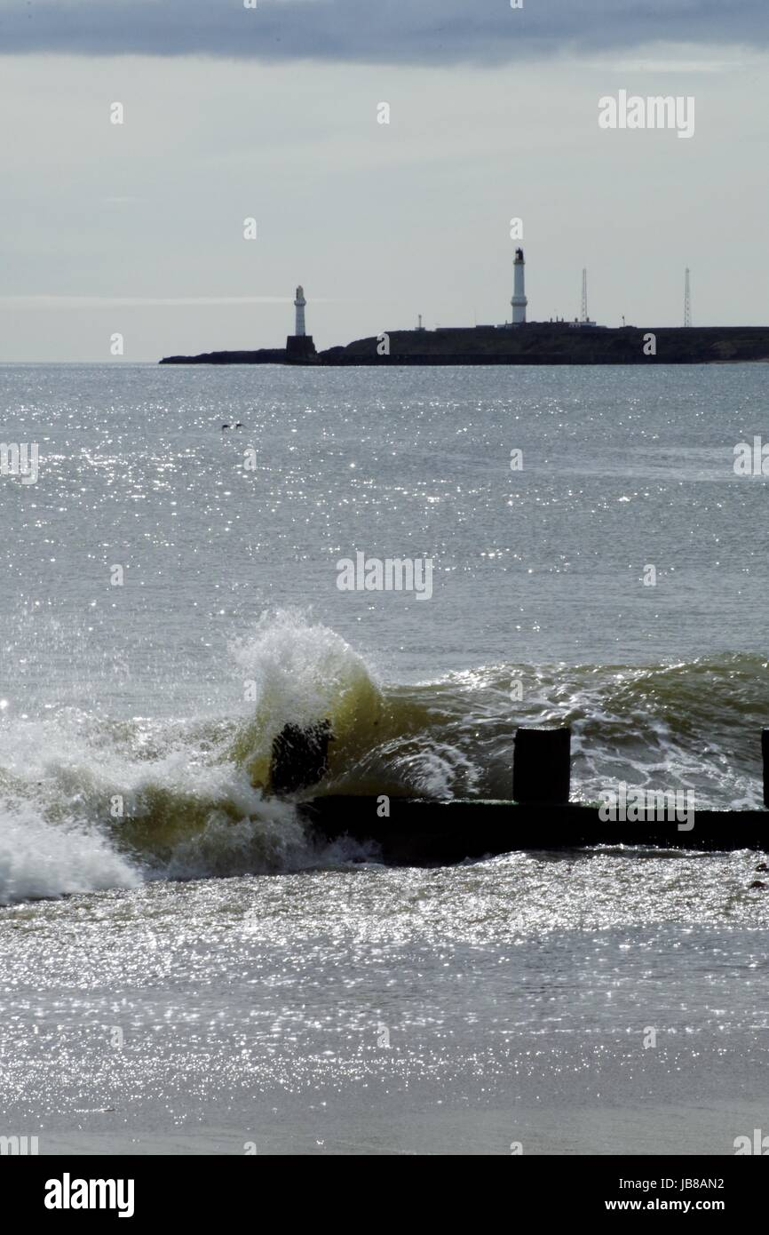 North Sea Waves Striking the Beach at Aberdeen, with Girdle Ness Lighthouse in the Distance. Scotland, April 2017. Stock Photo