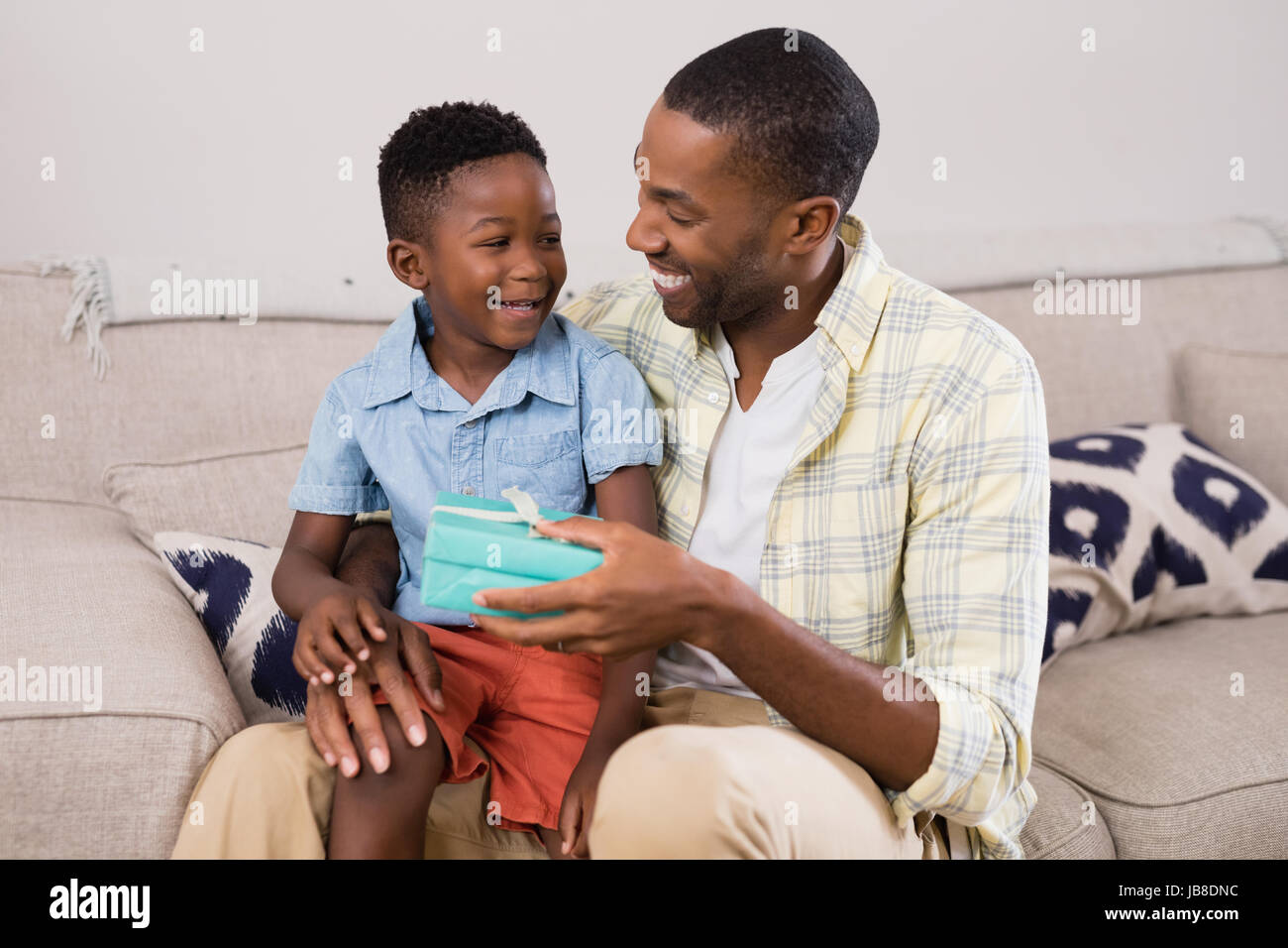 Cheerful father exchanging gift box on sofa at home - Stock Image
