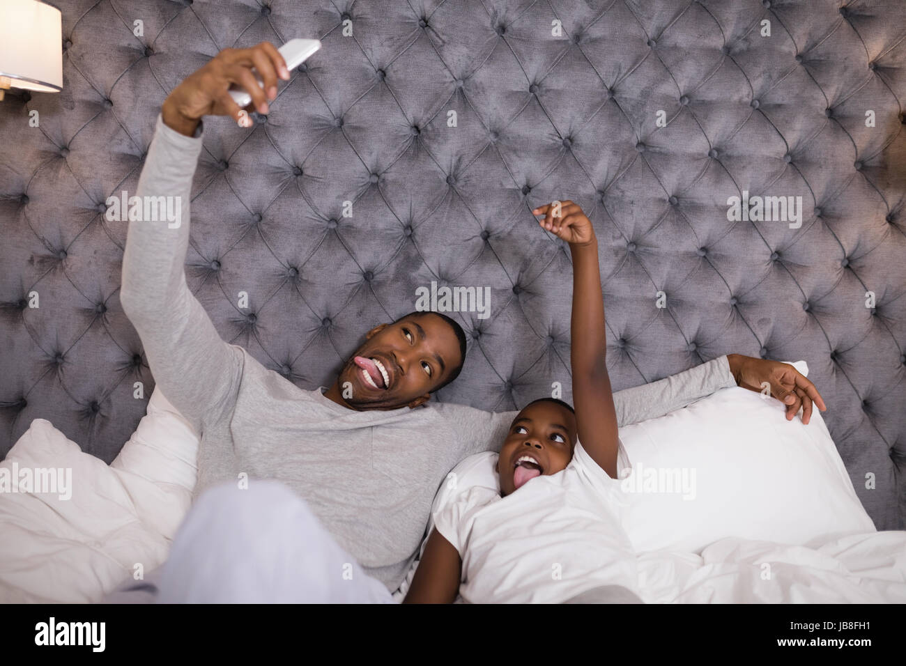 Mischievous father and son taking selfie while lying on bed at home - Stock Image
