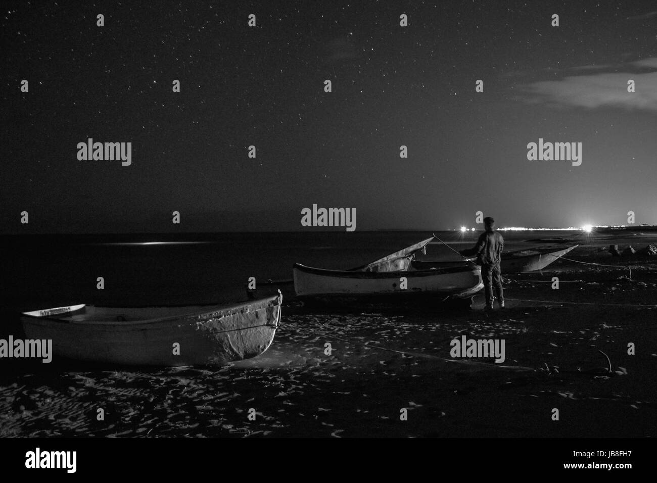 Man in the middle of the boats looks at the starry sky - Stock Image
