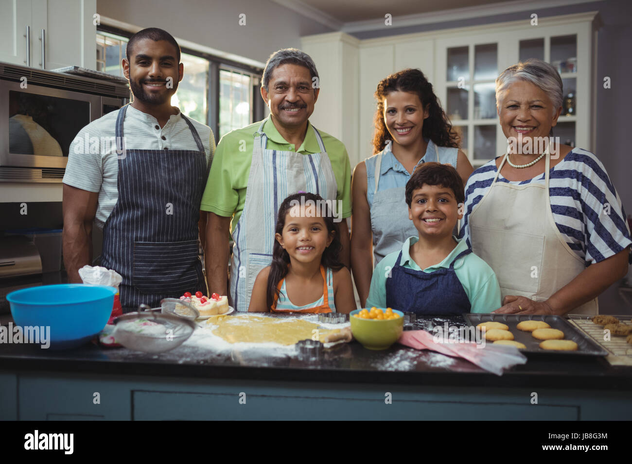 Portrait of happy family preparing dessert in kitchen at home - Stock Image