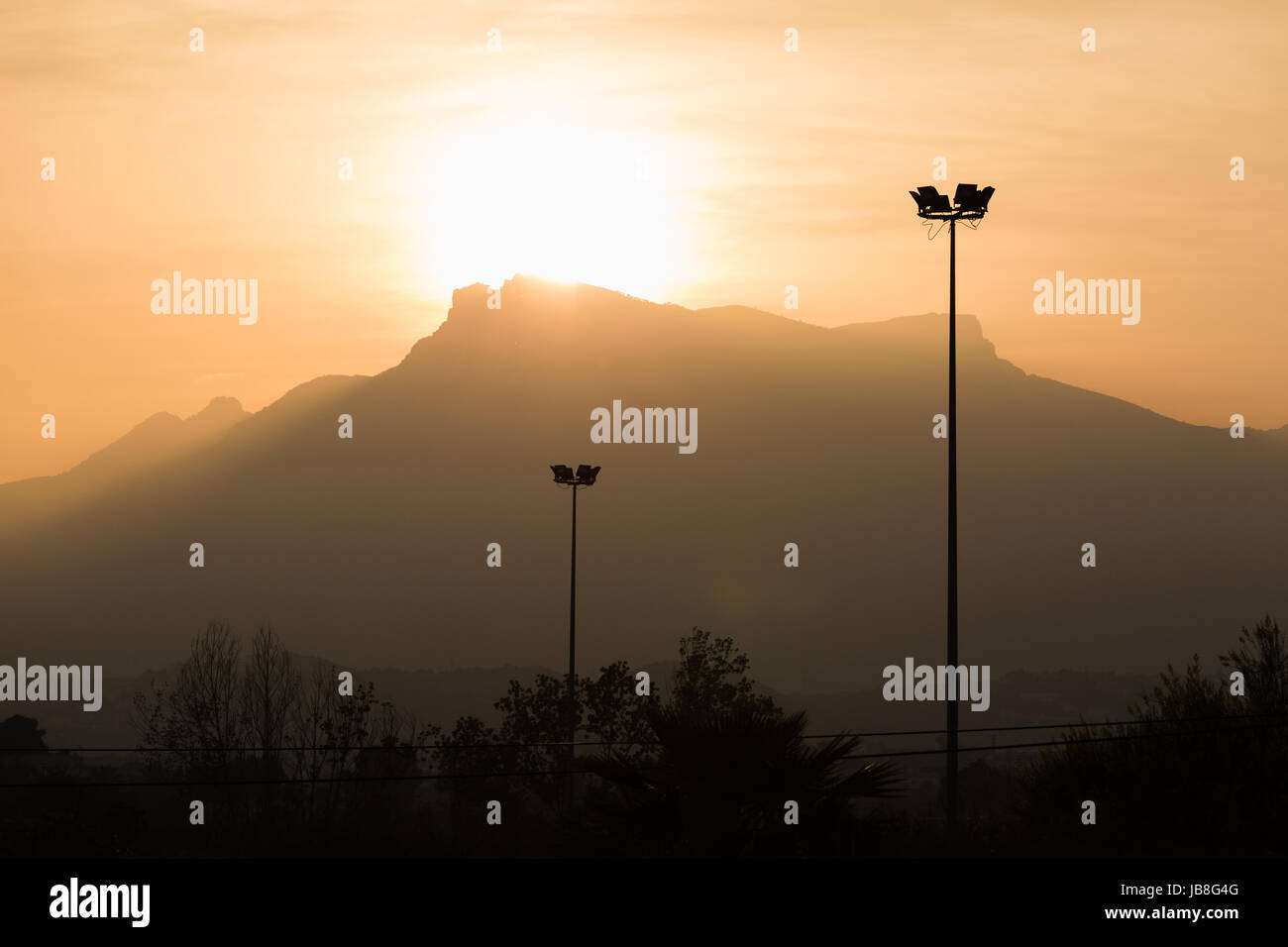 Telegraph poles cables in the sunset with mountains in the background - Stock Image