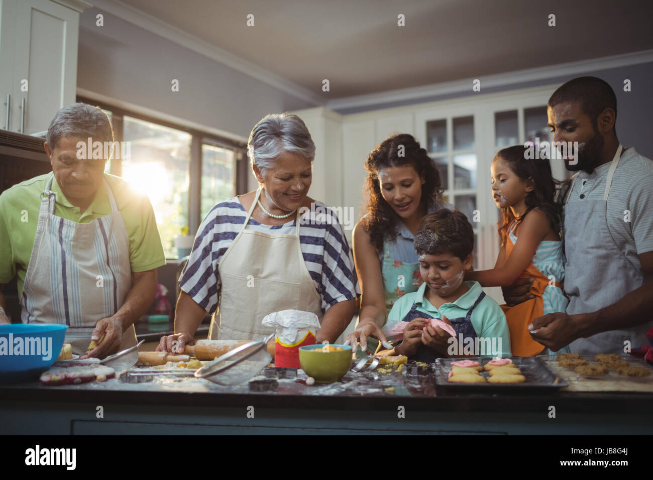 Happy family preparing dessert in kitchen at home Stock Photo
