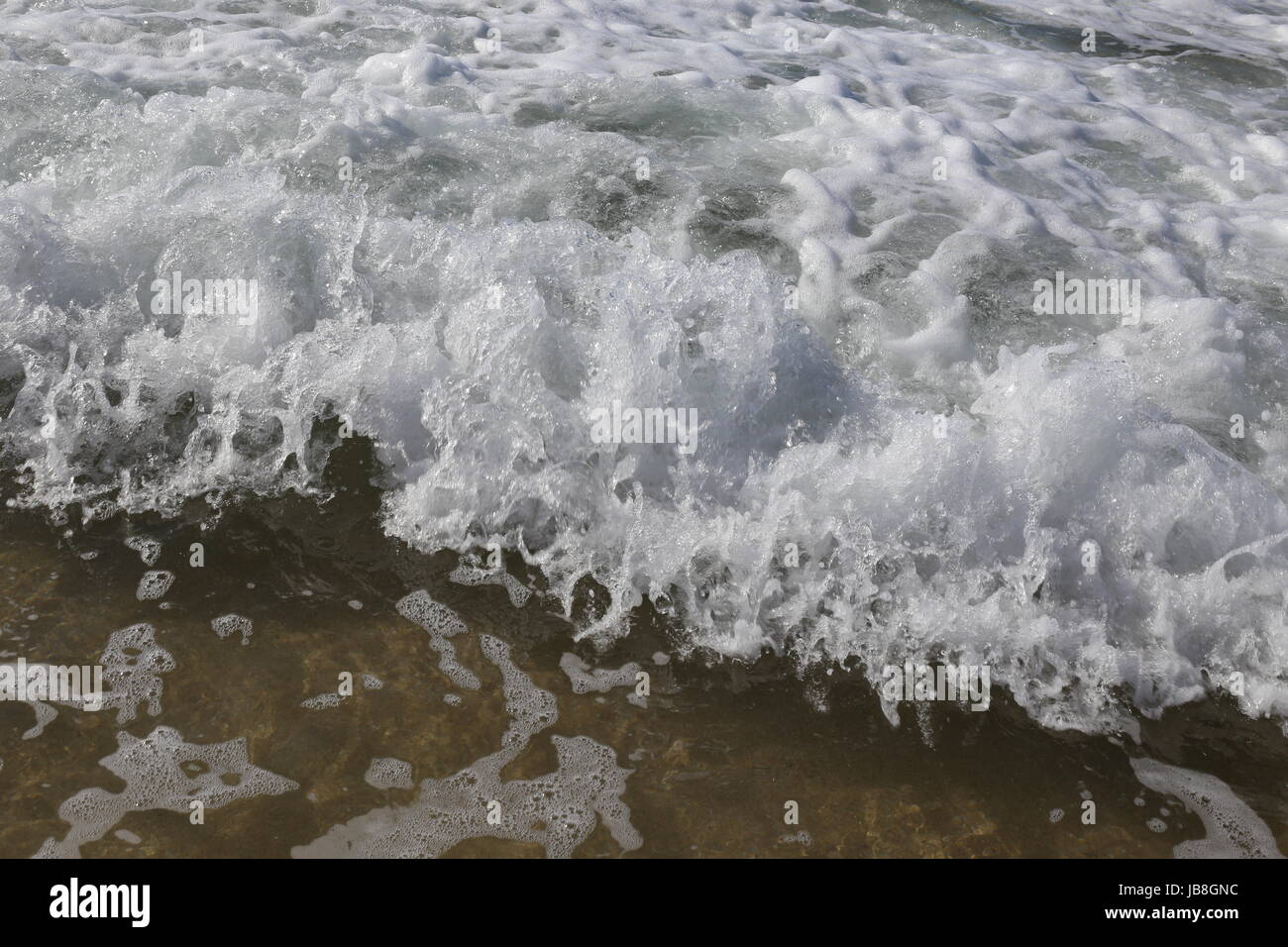 Close up of breaking wave lapping the shore - Stock Image